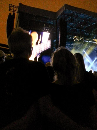 50-somethings lock arms at a Paul McCartney concert