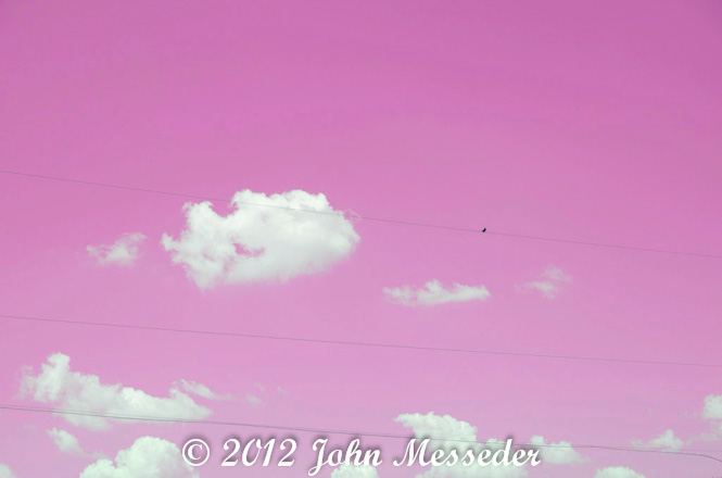White puffy clouds float through a pink sky