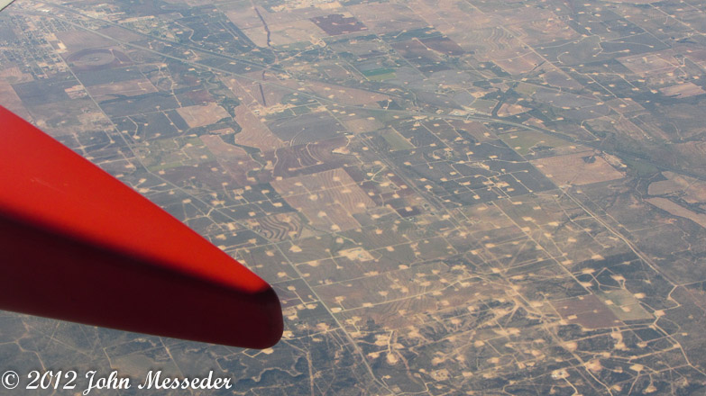 From 30,000 feet, Texas oil fields look like electronics circuit boards overlaid on homes and crops.