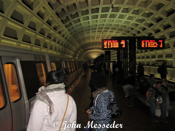 Commuters wait to board the arriving light rail in the Washington Metro station