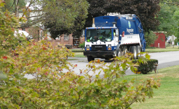 Trash collection truck transports municipal waste to landfill.