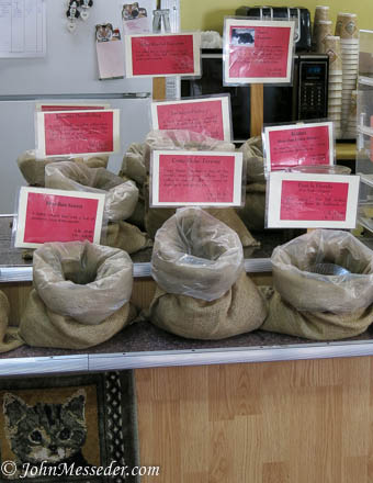 Plastic-lined burlap bags of in-house roasted coffee beans wait to be brewed