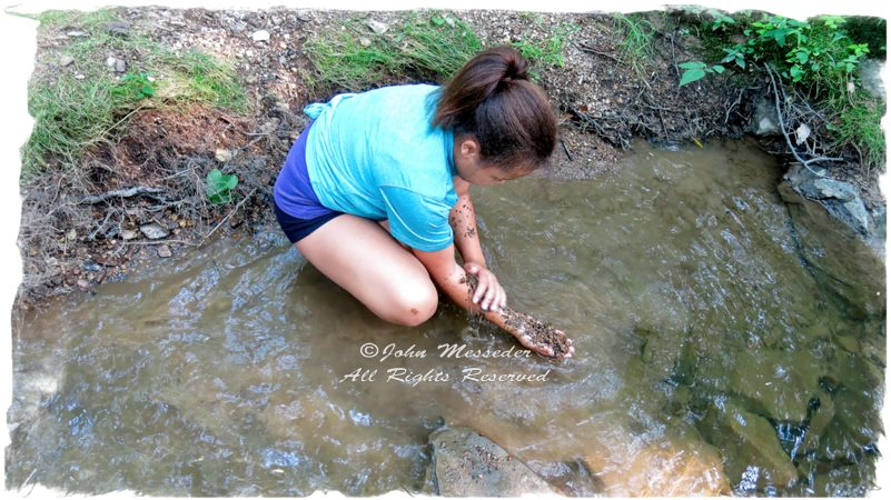 youngster rubbing creek gravel on her arm