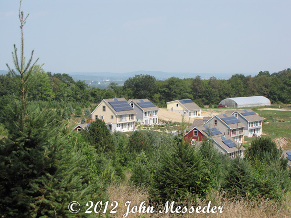 Hillside development features rooftop solar panels and natural wastewater treatment