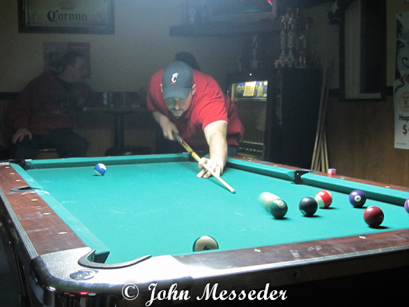 A player takes aim at the pool table, observers behind him barely visible in the smoky haze