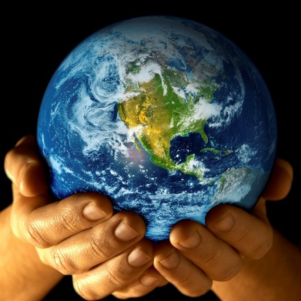 Hands cradle the Earth